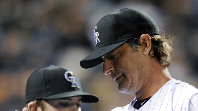 Colorado Rockies starting pitcher Jamie Moyer is congratulated by teammates in the sixth inning of a baseball game against the San Diego Padres on Tuesday, April 17, 2012 in Denver. The Rockies won 5-3. Jamie Moyer became the oldest pitcher to win a major league game. (AP Photo/Chris Schneider)