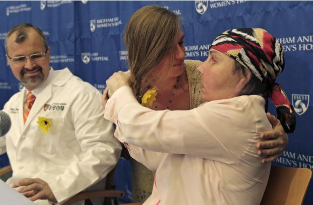 Carmen Blandin Tarleton of Thetford, Vermont, right, is embraced by Marinda Righter, daughter of face donor Cheryl Denelli-Righter, at Brigham and Women's Hospital in Boston, Mass., Wednesday, May 1,