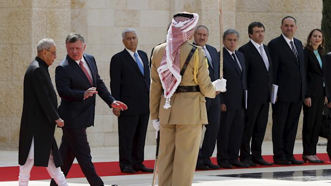 Abdullah and Mukherjee walk to review an honour guard before their meeting at the Royal Palace in Amman