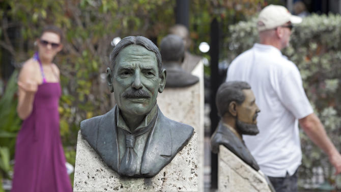 In this Wednesday, March 13, 2013, photo provided by the Florida Keys News Bureau, visitors walk in the Key West Historic Memorial Sculpture Garden behind a bust of Henry Flagler in Key West, Fla. The free-admission gardens features 38 bronze busts of prominent men and women who had a key influence on the development of Key West and the remainder of the Florida Keys. Flagler developed the Florida Keys Oversea Railroad more than 100 years ago that linked mainland Florida with the island chain. (AP Photo/Florida Keys News Bureau, Carol Tedesco)
