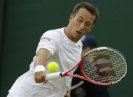 Philipp Kohlschreiber of Germany plays a shot to Brian Baker of the United States during a fourth round singles match at the All England Lawn Tennis Championships at Wimbledon, England, Tuesday, July 3, 2012. (AP Photo/Alastair Grant)