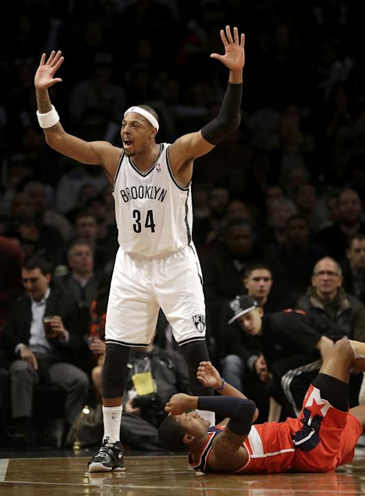 Brooklyn Nets' Paul Pierce, left, reacts after fouling Washington Wizards' Bradley Beal during the second half of an NBA basketball game Wednesday, Dec. 18, 2013, in New York. Washington defea