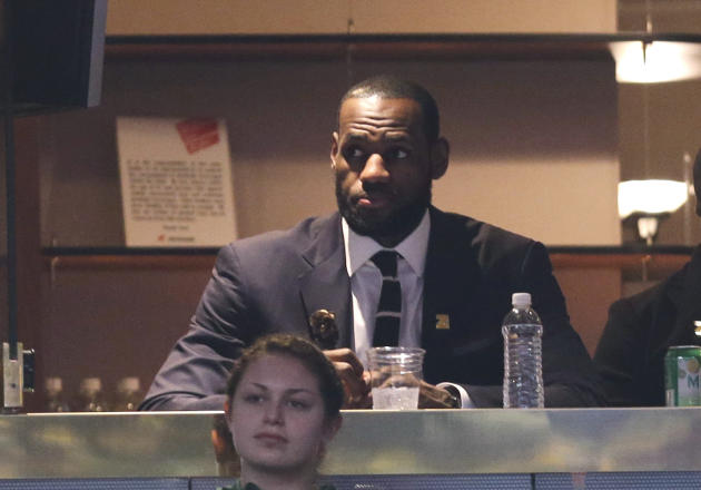 Miami Heat's LeBron James watches an NBA basketball game between the New York Knicks and the Cleveland Cavaliers on Saturday, March 8, 2014, in Cleveland