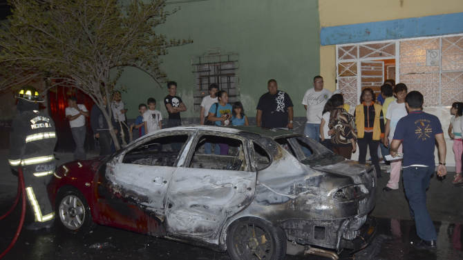 People stand in front of a partially burned vehicle after gunmen shot and killed an as of yet undetermined number of people in the Tepito neighborhood in Mexico City, Thursday June 6, 2013. (AP Photo)