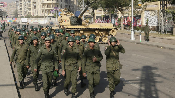 "Soldiers walk past a military tank guarding the presidential palace in Cairo, Egypt, Thursday, Dec. 13, 2012. Egypt's opposition called on its followers to vote ""no"" in a crucial referendum on a disputed constitution drafted by Islamist supporters of President Mohammed Morsi. (AP Photo/Hassan Ammar)"