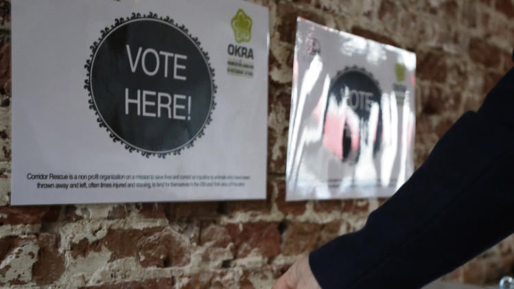 In this Jan. 16, 2013 photo, a patron drops a ticket into a voting box at the Original OKRA Charity Saloon in Houston. The new downtown bar is offering its customers a relaxed atmosphere with good drinks and food and a pledge that 100 percent of its profits after costs will be donated to a different local charity or social cause each month. Patrons are given a ticket for each purchase to vote with. (AP Photo/Pat Sullivan)