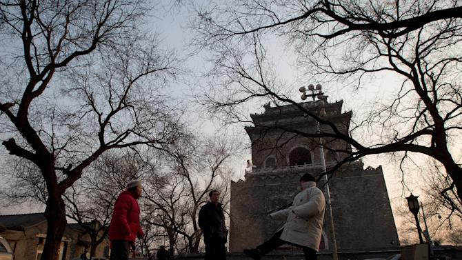 In this photo taken on Dec. 26, 2012, resident plays Jianzi, a Chinese traditional game at the square near the historical Drum and Bell Tower, seen in the background, in Beijing. The district government wants to demolish scuffed courtyard homes, move their occupants to bigger apartments farther from the city center and redevelop a square in 18th century Qing Dynasty fashion.(AP Photo/Andy Wong)