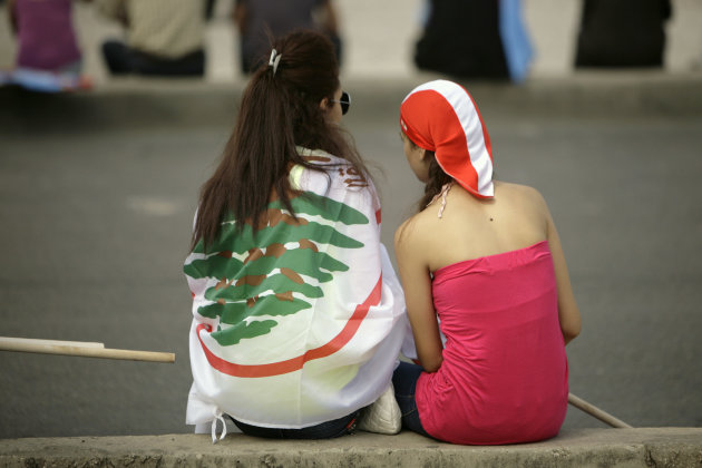 Two young Lebanese women, one draped in the national flag, wait in Martyrs' Square for the funeral for the country's intelligence chief, Brig. Gen. Wissam al-Hassan in Beirut, Lebanon, Sunday, Oct. 21