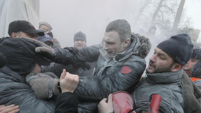 FILE - In this Sunday, Jan. 19, 2014. file photo opposition leader and former WBC heavyweight boxing champion Vitali Klitschko, center, is attacked and sprayed with a fire extinguisher as he tries to stop the clashes between police and protesters in central Kiev, Ukraine. After two months of anti-government protests, modern Ukraine has never been so bitterly polarized. To be sure, Ukraine has long been divided. Russia and Europe have vied for dominance for centuries, causing deep cultural differences between the mostly Ukrainian-speaking western and central regions on the one hand, and the Russian-speaking east and south on the other. But as the crisis has deepened, each side has grown stronger in its convictions, and those who stood in the middle have been forced to choose sides. (AP Photo/Efrem Lukatsky, file)