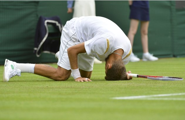 Martin Klizan of Slovakia slips during his men's singles tennis match against Tomas Berdych of the Czech Republic at the Wimbledon Tennis Championships, in London