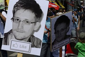 Demonstrators hold images of Edward Snowden at a rally …