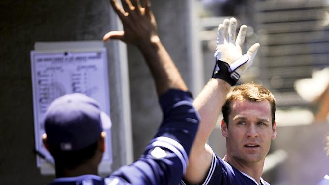 San Diego Padres' Logan Forsythe, right, celebrates with Jesus Guzman after scoring off of a throwing error by Los Angeles Dodgers second baseman Mark Ellis in the fourth inning of a baseball game, Sunday, July 15, 2012, in Los Angeles. (AP Photo/Gus Ruelas)