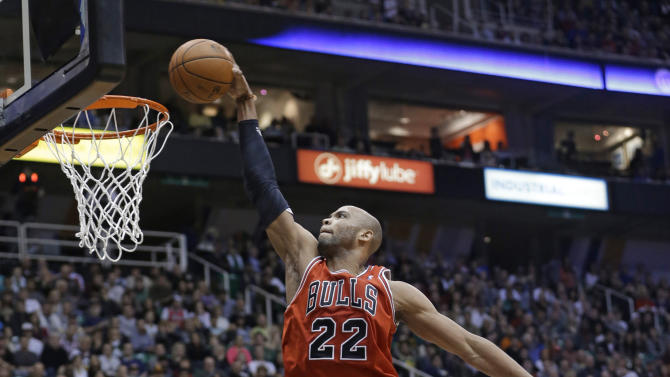 Chicago Bulls' Taj Gibson (22) dunks as Utah Jazz's Randy Foye (8) and Enes Kanter (0) watch during the second quarter of an NBA basketball game Friday, Feb. 8, 2013, in Salt Lake City. (AP Photo/Rick Bowmer)