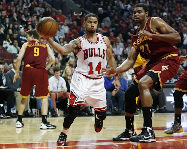 Chicago Bulls guard D.J. Augustin (14) passes past Cleveland Cavaliers center Andrew Bynum (21) during the second half of an NBA basketball game on Saturday, Dec. 21, 2013, in Chicago