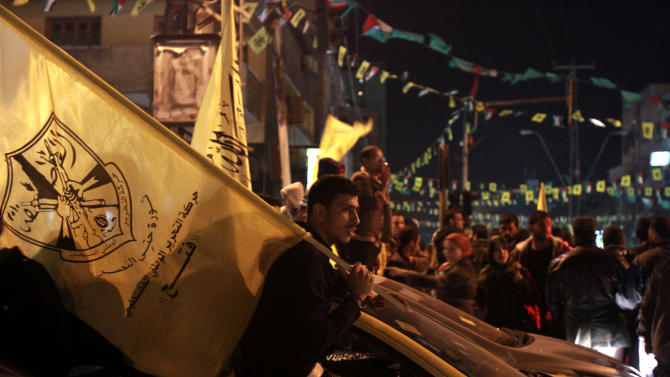 A Palestinian man holds a Fatah flag during celebrations marking the 48th anniversary of the Fatah movement in Gaza City, Thursday, Jan. 3, 2013. (AP Photo/Adel Hana)