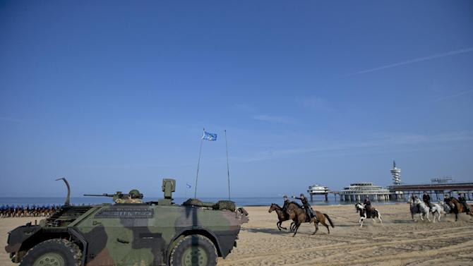 The Dutch cavalry charges as it follows an armored vehicle as they arrive for a practice session in Scheveningen, Netherlands, Monday, Sept. 15, 2014. About 80 horses and riders were rehearsing on a beach in the coastal resort of Scheveningen, outside The Hague, for ceremonies which will be held Tuesday to mark the opening of parliament. The horses were exposed to smoke grenades and harsh sounds to reduce their chances of being startled by any incidents during the ceremony. (AP Photo/Peter Dejong)