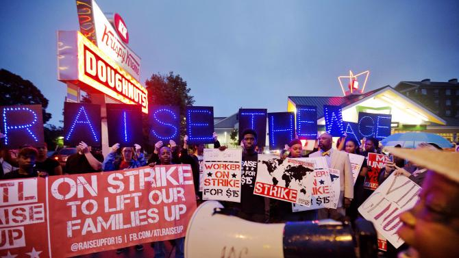 McDonald's employee Connie Ogletree, 55, right, leads a group of fast food workers and supporters in a chant during a protest outside a Krispy Kreme store, Thursday, May 15, 2014, in Atlanta. Calling for higher pay and the right to form a union without retaliation, fast-food chain workers in Atlanta protested Thursday as part of a wave of strikes and protests in 150 cities across the U.S. and 33 additional countries on six continents. (AP Photo/David Goldman)