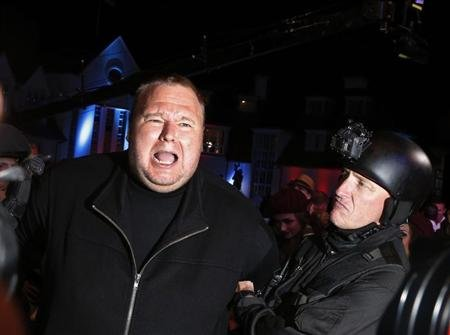 "An actor in police costume mock-arrests Kim Dotcom as he launches his new website ""Mega"" in Auckland"