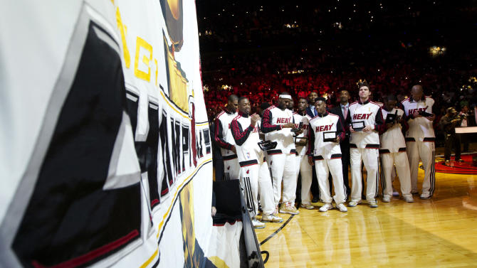 Miami Heat players hold their 2012 NBA Finals championship rings as they stand next to the championship banner during a ceremony before a basketball game against the Boston Celtics, Tuesday, Oct. 30, 2012, in Miami. (AP Photo/J Pat Carter)