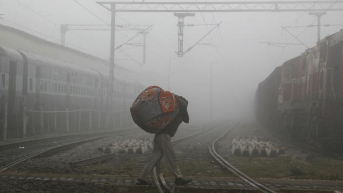 A man carries blankets as he crosses railway tracks on a foggy and cold winter morning in Allahabad