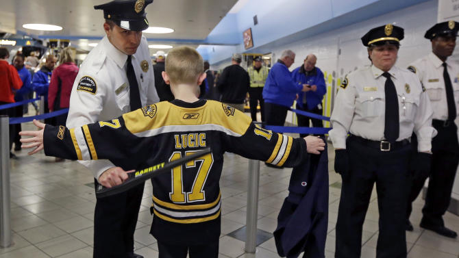 FILE - A young Boston Bruins fan raises his arms for a security check on the way into TD Garden abefore a Bruins NHL hockey game against the Buffalo Sabres in Boston on Wednesday, April 17, 2013, in the aftermath of Monday's Boston Marathon bombings. (AP Photo/Elise Amendola)