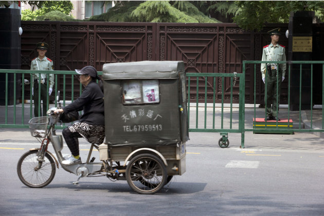 A Chinese man on a tricycle moves past the North Korean embassy in Beijing, China, Wednesday, May 22, 2013. North Korean leader Kim Jong Un dispatched a high-profile official and close confidant to tr