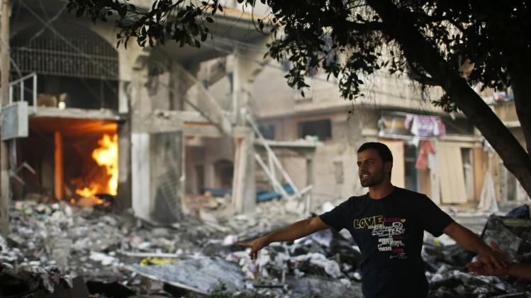 A Palestinian man reacts after what police said was an Israeli air strike on a house, in Gaza City
