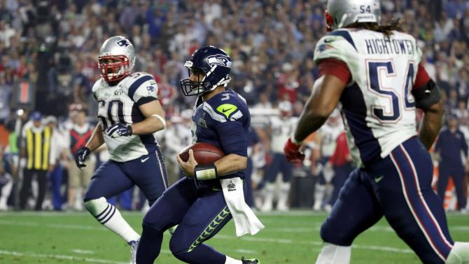 Seattle Seahawks quarterback Wilson runs for a first down in the third quarter between New England Patriots outside linebacker Hightower and defensive end Ninkovich during the NFL Super Bowl XLIX football game in Glendale