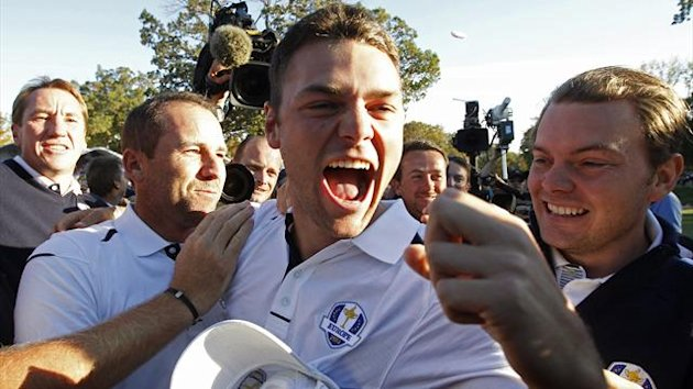 Team Europe golfer Martin Kaymer (C) of Germany celebrates winning his match against U.S. golfer Steve Stricker to retain the Ryder Cup for Europe with teammate Sergio Garcia (L) of Spain (Reuters)
