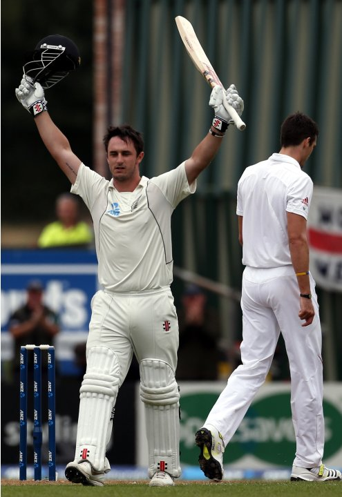 New Zealand's Rutherford celebrates making his century as England's Finn walks away during the third day of the first test at the University Oval in Dunedin