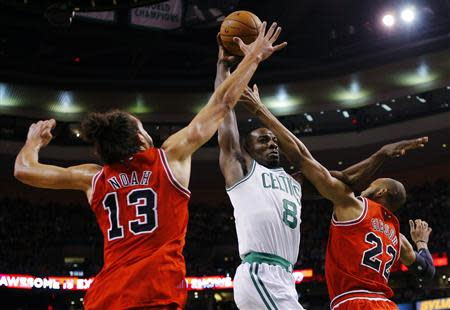 Boston Celtics' Green drives to the basket between Chicago Bulls' Noah and Gibson in their NBA basketball game in Boston