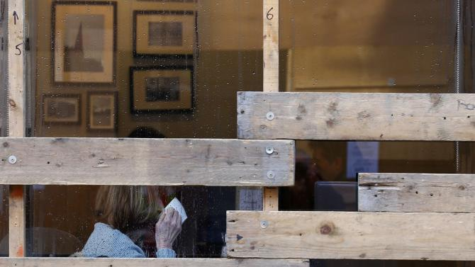 A woman drinks behind partially boarded windows of a shop before the annual Shrovetide football match in Ashbourne