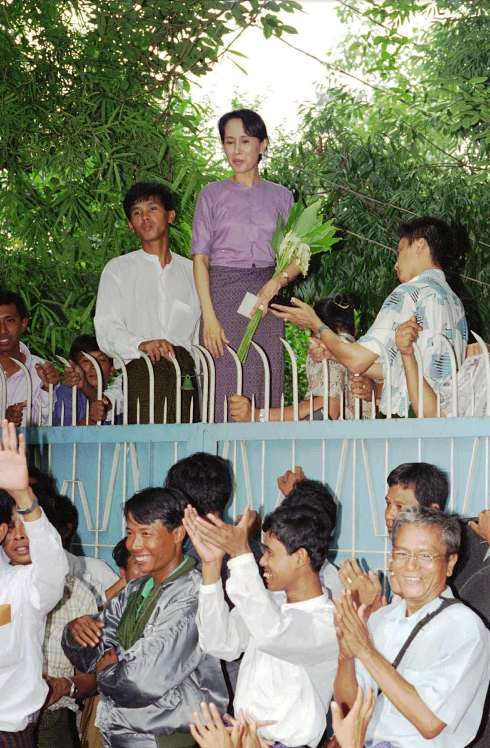 FILE - In this Tuesday, July 11, 1995 file photo, Aung San Suu Kyi stands behind her gate to greet a crowd of about 1,000 people who came to see her in Rangoon, Burma. (AP Photo/Stuart Isett)