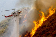 A Los Angeles County Firefighter helicopter drops water on a wildfire burning through 3,600 acres of the Angeles National Forest on Tuesday Sept. 4, 2012 near Glendora, Calif. It could be a week before firefighters can contain the blaze because of high temperatures and rugged terrain in thick brush that hasn&#39;t burned in a couple of decades. (AP Photo/Nick Ut)