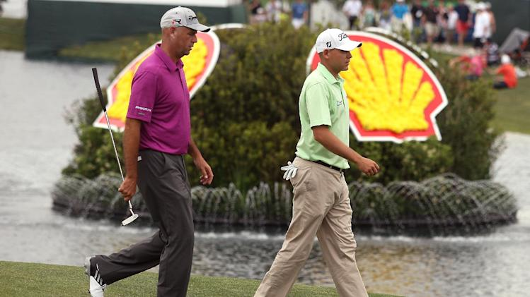 Stewart Cink, left, and Bill Haas walk off the 18th green after finishing the third round of the Houston Open golf tournament, Saturday, March, 30, 2013, in Humble, Texas. (AP Photo/ Patric Schneider)