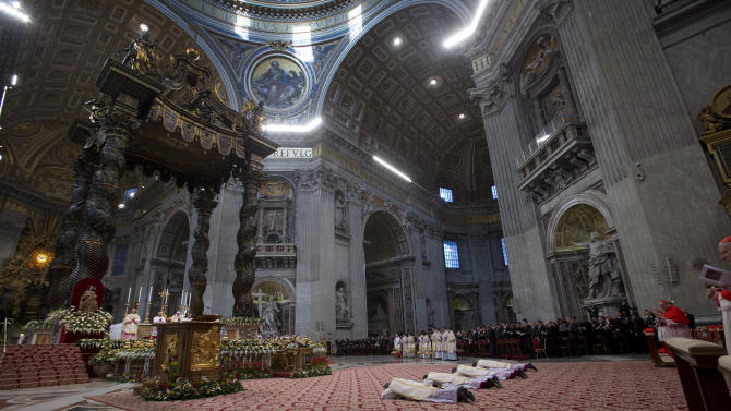 From left, Angelo Vincenzo Tani, of Italy, Fortunatus Nwachukwu, of Nigeria, Georg Ganswein, of Germany, and Nicolas Marie Denis Thevenin lie on the ground as they are named bishops during an Epiphany mass celebrated by Pope Benedict XVI in St.Peter's Basilica at the Vatican, Sunday, Jan. 6, 2013. The Epiphany day, is a joyous day for Catholics in which they recall the journey of the Three Kings or Magi to pay homage to Baby Jesus. (AP Photo/Andrew Medichini)
