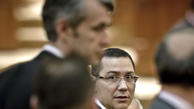 FILE - A file picture taken on May 7, 2012, Romanian Premier designate Victor Ponta, right, is seen before a parliament session in Bucharest, Romania. Romania's president on Monday, Dec. 17, 2012, reappointed the prime minister to his post despite a bitter feud between the two top officials. Traian Basescu said he had designated Victor Ponta as prime minister after Ponta's center-left governing alliance won some 68 percent of seats in Dec. 9 parliamentary elections. (AP Photo/Vadim Ghirda, File)