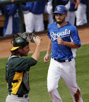 Kansas City Royals' Eric Hosmer runs home past Oakland Athletics catcher John Jaso to score on a double by Mike Moustakas during the first inning of an exhibition spring training baseball game Tuesday, March 5, 2013, in Surprise, Ariz. (AP Photo/Charlie Riedel)