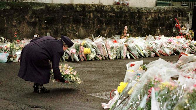FILE - In this March 17, 1996 file photo, Britain's Queen Elizabeth places a floral bouquet with hundreds of others in front of Dunblane Primary School. In March 1996, a 43-year-old man named Thomas Hamilton walked into a primary school in this central Scotland town of 8,000 people and shot to death 16 kindergarten-age children and their teacher with four legally held handguns. In the weeks that followed, people in the town formed the Snowdrop campaign - named for the first flower of spring - to press for a ban on handguns. Within weeks, it had collected 750,000 signatures. By the next year, the ban had become law. (AP Photo/Ian Waldie, Pool-File)