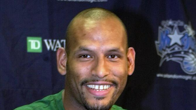 """FILE- John Amaechi, the first British player to start in an NBA game, playfully covers a tee shirt that states """"Amaechi Tea Co."""" at a news conference in Orlando, Fla. USA, in this file photo dated Tuesday Aug. 8, 2000.  Amaechi became the first openly gay former NBA player with a landmark public statement in 2007, three years after retiring, but in a telephone interview with The Associated Press, Amaechi disclosed that he is in contact with gay English Premier League players to advise them about gay issues. (AP Photo/Peter Cosgrove, File)"""