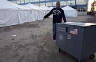 Voting equipment is dragged across dried mud and sand towards tents that have become a make shift voting locations at Scholars&#39; Academy, PS 180, in the Rockaway neighborhood of the borough of Queens, New York, Monday, Nov. 5, 2012. Several normal voting sites have become unusable due to high water and wind damage in the wake of Superstorm Sandy. (AP Photo/Craig Ruttle)