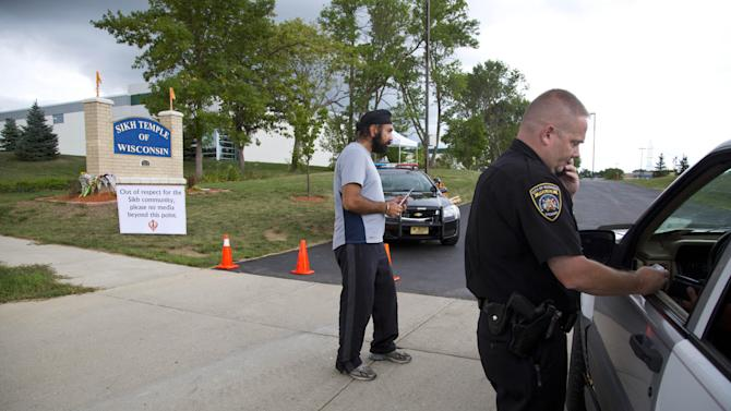 Police check identifications as Members of the Sikh temple of Wisconsin are allowed to return for the first time in Oak Creek, Wis, Thursday, Aug 9, 2012.  The mass shooting last Sunday claimed six members of the temple. (AP Photo/Jeffrey Phelps)
