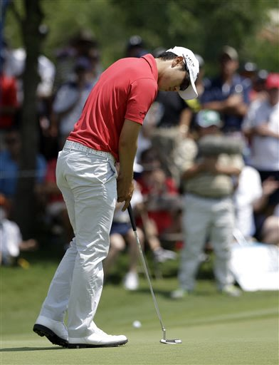 Sang-Moon Bae, of South Korea, reacts after sinking a putt on the second green during the third round of the Byron Nelson Championship golf tournament Saturday, May 18, 2013, in Irving, Texas