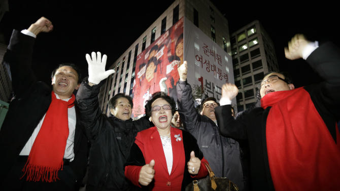 Supporters of South Korean presidential candidate Park Geun-hye of the ruling Saenuri Party cheer near the party's head office in Seoul, South Korea, Wednesday, Dec. 19, 2012. South Koreans voting for president Wednesday were almost evenly divided between the conservative daughter of a late dictator and the liberal son of North Korean refugees, according to surveys released after the polls closed. (AP Photo/Lee Jin-man)