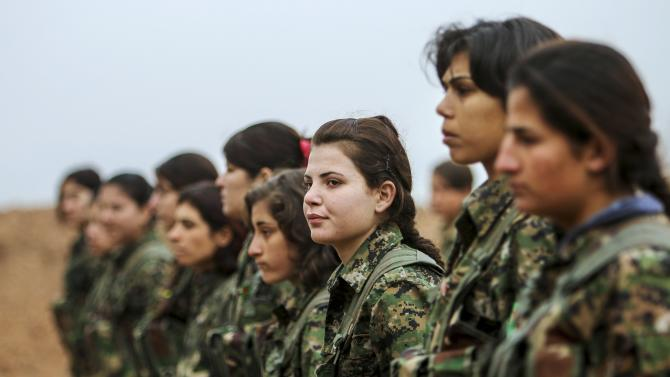 Female fighters of the Kurdish People's Protection Units stand at attention at a military camp in Ras a-Ain