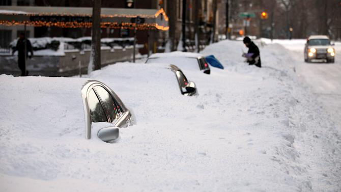 Buried cars shine as the sun rises in New York Monday, Dec. 27, 2010, in the wake of a blizzard that hammered the city and much of the Northeast. (AP Photo/Craig Ruttle)