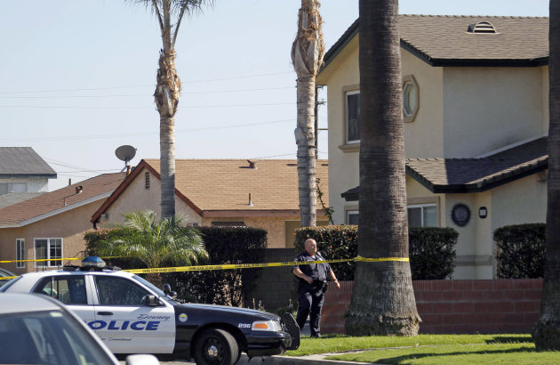A police officer stands outside a two-story home, right, where one person was found shot to death in Downey, Calif., Wednesday, Oct. 24, 2012. Five people were shot and at least two died in shootings
