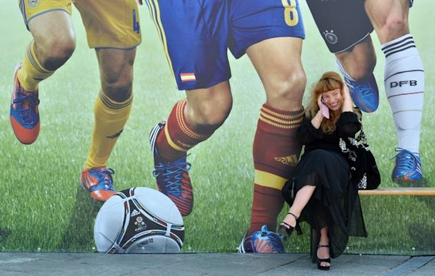 TOPSHOTS A Woman Smiles As She Speaks On The Phone In Front Of A Giant Poster Of Football In The Euro 2012 Fan Zone At  AFP/Getty Images