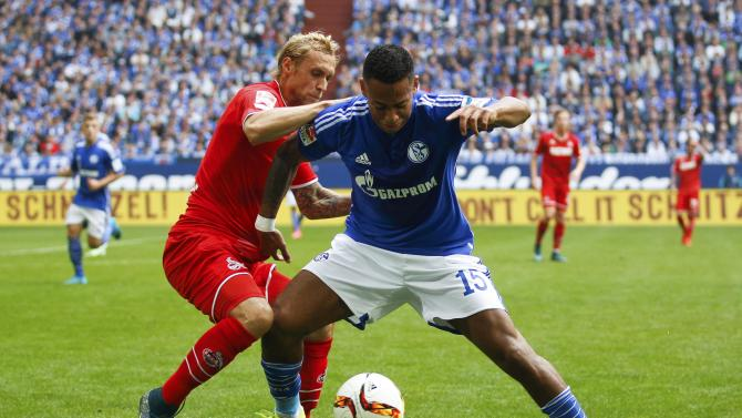Schalke 04's Aogo challenges 1.FC Cologne's Risse during their Bundesliga first division soccer match in Gelsenkirchen