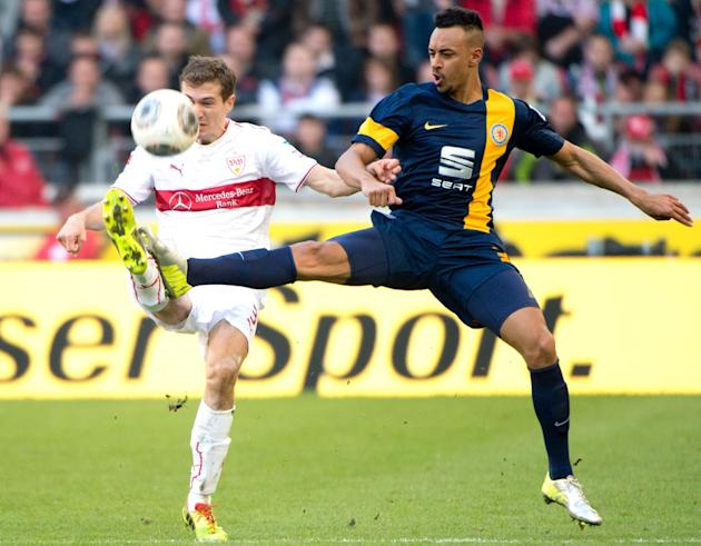 Stuttgart's Daniel Schwaab , left,  challenges for the ball with Braunschweig's Karim Bellarabi, during the German Bundesliga soccer match between VfB Stuttgart and Eintracht Braunschweig in S